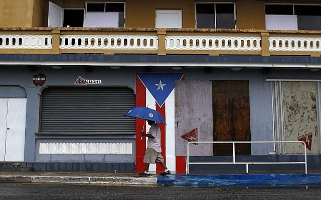 Un homme avec un parapluie marche sur un trottoir alors que l'ouragan Irma s'approche à Luquillo, Porto Rico, le 6 septembre 2017 (Crédit : Photo AFP / Ricardo Arduengo)