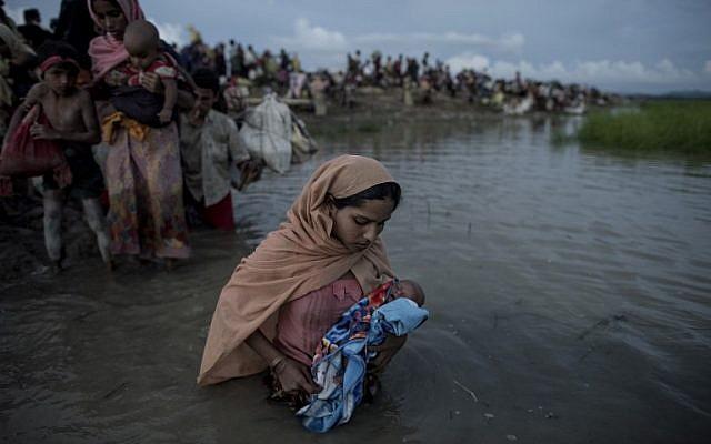 Des réfugiés rohingyas en train de porter des enfants après avoir traversé la rivière Naf du Myanmar au Bangladesh à Whaikhyang, le 9 octobre 2017 (AFP / Fred Dufour)