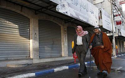 Illustration : Des Palestiniens marchent devant les magasins fermés dans la ville de Hébron en Cisjordanie, après un appel à la grève générale pour protester contre la décision prise par le président américain Donald Trump de reconnaître Jérusalem en tant que capitale d'Israël, le 7 décembre 2017 (Crédit : (HAZEM BADER/AFP)