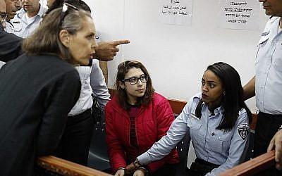 Nour Tamimi (C), qui est détenue après une vidéo virale montrant deux membres de sa famille en train d'agresser deux soldats israéliens, dans un tribunal militaire à la prison d'Ofer en Cisjordanie le 28 décembre 2017 (Crédit : Ahmad Gharabli / AFP)