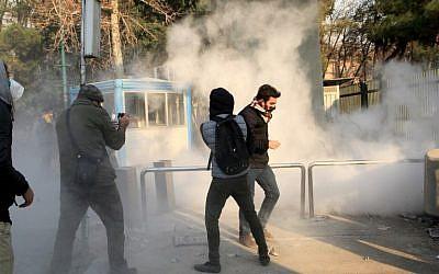 Des étudiants fuient les tirs de gaz lacrymogènes devant l'université de Téhéran durant une manifestation contre les problèmes économiques dans la capitale iranienne, le 30 décembre 2017. Les étudiants ont manifesté pour un troisième jour en raison des problèmes de l'économie iranienne, comme l'ont montré des vidéos sur les réseaux sociaux. Mais leur nombre a été surpassé par les contre-manifestants (Crédit :  AFP / STR)