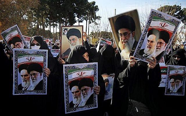 Des manifestants pro-gouvernementaux brandissent des affiches du leader suprême iranien, l'ayatollah Ali Khamenei et du fondateur iranien de la République islamique, l'ayatollah Ruhollah Khomeiny, lors d'une marche dans la ville sainte iranienne de Qom le 3 janvier 2018 (Crédit : AFP PHOTO / Mohammad ALI MARIZAD)