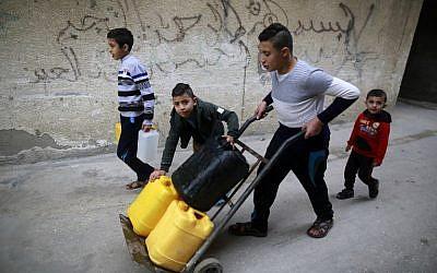 Des enfants palestiniens transportent des bidons d'eau dans le camp de réfugiés d'al-Shati dans la ville de Gaza le 4 janvier 2018 (Crédit : AFP PHOTO / MOHAMMED ABED)