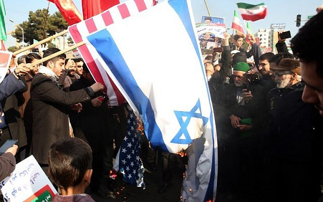 Les manifestants iraniens pro-régime ont brûlé les drapeaux israéliens et américains lors d'un rassemblement en faveur du régime après que les autorités ont déclaré la fin des troubles meurtriers, dans la ville de Mashhad le 4 janvier 2018, (Crédit : PHOTO AFP / NOUVELLES TASNIM / NIMA NAJAFZADEH)
