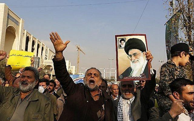 Des manifestants pro-gouvernementaux tiennent un poster du chef suprême iranien, l'Ayatollah Ali Khamenei, et scandent des slogans durant une manifestation qui a suivi les prières musulmanes du vendredi à Téhéran le 5 janvier 2018 (Crédit : AFP Photo/Atta Kenare)