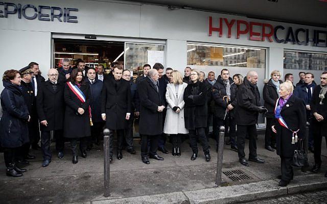 La maire de Paris Anne Hidalgo (4ème g), le président français Emmanuel Macron (5ème g), le ministre français de l'Intérieur Gérard Collomb (6ème), le porte-parole du gouvernement français Benjamin Griveaux (C), la femme du président Brigitte Macron (6ème) rendent hommage lors d'une cérémonie commémorative devant le supermarché Hyper Casher aux victimes du magasin casher qui ont été tuées il y a trois ans par un terroriste islamiste à Paris, le 7 janvier 2018. (Crédit : AFP / POOL / CHRISTIAN HARTMANN)