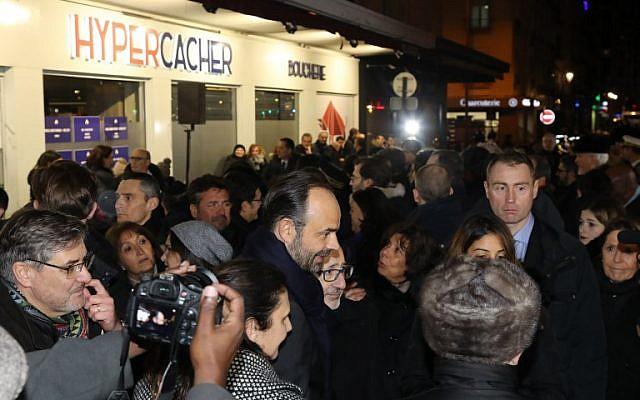Le Premier ministre français Edouard Philippe entouré des familles des victimes lors d'un hommage aux victimes de la prise d'otage au supermarché HyperCacher à Vincennes, le 9 janvier 2018, organisé par le Crif, à l'occasion du troisième anniversaire de l'attentat. (Crédit : AFP / POOL / JACQUES DEMARTHON)