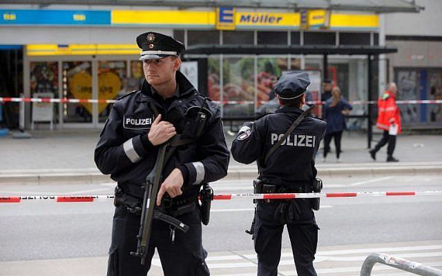 Des policiers montent la garde devant un supermarché à Hambourg, en Allemagne, où un homme a tué une personne et en a blessé six autres lors d'une attaque au couteau, le 28 juillet 2017 (Crédit : AFP / DPA / Markus Scholz)