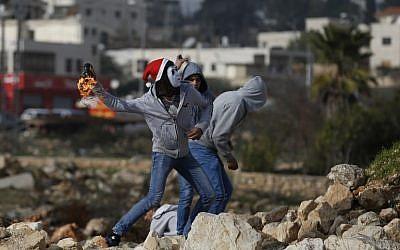 Illustration : des manifestants Palestiniens lancent des bombes incendiaires en directions des soldats israéliens durant des affrontements à Ramallah, en Cisjordanie, le 12 janvier 2018. (Crédit : AFP/ ABBAS MOMANI)