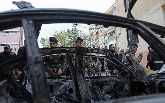 Les forces de sécurité libanaises contrôlent un véhicule incendié à la suite de l'explosion d'une voiture piégée dans la ville portuaire de Sidon, au sud du Liban, le 14 janvier 2018 (AFP PHOTO / Mahmoud ZAYYAT)