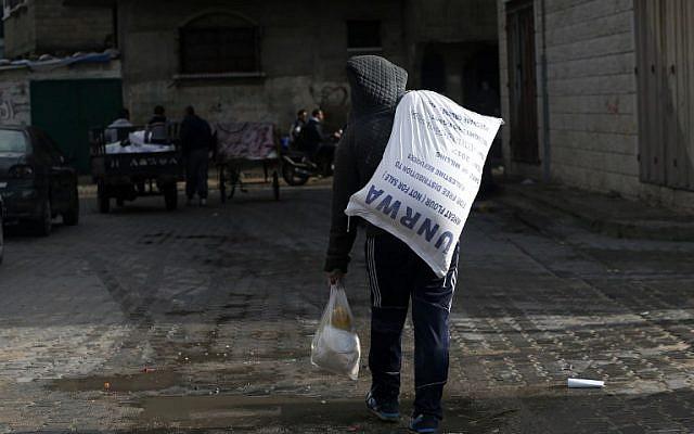 Un jeune Palestinien transporte un colis alimentaire de l'UNRWA à Gaza City, le 15 janvier 2018. (Crédit : MOHAMMED ABED / AFP)
