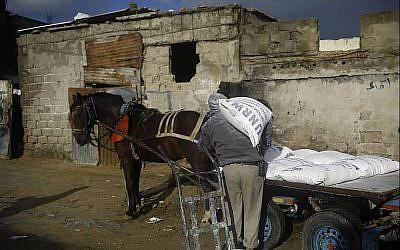 Un Palestinien remplit sa carriole d'aide alimentaire aux abords du centre de distribution des Nations unies à Gaza, le 28 janvier 2018 (Crédit :  AFP Photo/Mohammed Abed)