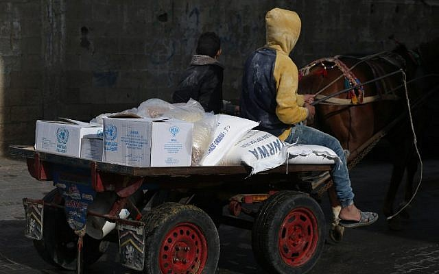 Un jeune Palestinien tire une charrette remplie de nourriture de l'UNRWA devant le centre de distribution alimentaire des Nations unies à Gaza le 15 janvier 2018 (AFP PHOTO / MOHAMMED ABED)