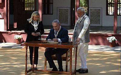 Le Premier ministre Benjamin Netanyahu (C) signe un livre d'or avec son épouse Sara Netanyahu et le Premier ministre indien Narendra Modi lors d'une visite à l'ashram de Gandhi à Ahmedabad le 17 janvier 2018. (AFP Photo / Sam Panthaky)
