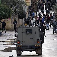 Des jeunes palestiniens jettent des pierres sur les forces israéliennes durant une opération militaire dans la ville de Jénine, en Cisjordanie, le 18 janvier 2018. (Crédit : AFP/Jaafar Ashtiyeh)