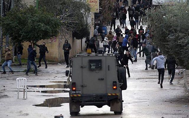 Des jeunes palestiniens jettent des pierres aux forces israéliennes durant une opération militaire dans la ville de Jénine, en Cisjordanie, le 18 janvier 2018 (Crédit : AFP/Jaafar Ashtiyeh)