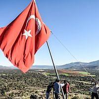 Des villageois réparent un drapeau turc, dans le village de Sugedik dans la province de, près de la frontière syrienne, le 20 janvier 2018.  (Crédit :AFP PHOTO / BULENT KILIC)
