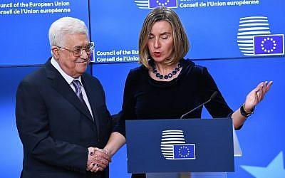 Le président de l'Autorité palestinienne Mahmoud Abbas, à gauche, est accueilli par la cheffe de la politique étrangère de l'UE Federica Mogherini avant un conseil des ministres des Affaires étrangères européens à la Commission européenne de Bruxelles, le 22 janvier 2018 (Crédit : EMMANUEL DUNAND / AFP)