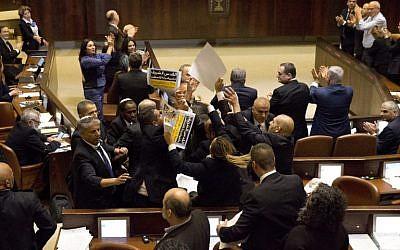 """Les députés de la Liste arabe unie brandissent des pancartes sur lesquelles est écrit """"Jérusalem est la capitale de la Palestine"""" lors du discours du vice-président américain Mike Pence à la Knesset à Jérusalem le 22 janvier 2018. (Photo AFP / Pool / Ariel Schalit)"""