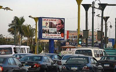 Les Égyptiens passent devant un panneau d'affichage arborant l'image du président égyptien Abdel-Fattah el-Sissi, dans le cadre de la campagne pour sa réélection aux prochains scrutins prévus pour le mois de mars 2018, le 22 janvier 2018, au Caire (Crédit : PHOTO AFP / MOHAMED EL-SHAHED)