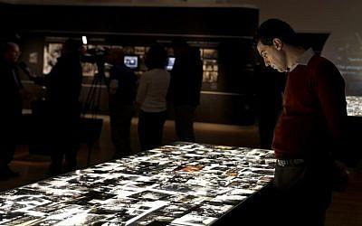 """Un homme regarde les photos de l'exposition """"Flash mémoriel"""" offre trois perspectives divergentes sur l'Holocauste: celle des nazis, des victimes juives et des soldats des forces alliées, à Yad Vashem, à Jérusalem, le 24 janvier 2018. (Crédit : GALI TIBBON / AFP)"""