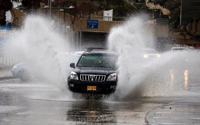 Les automobilistes conduisent à travers les rues inondées après une tempête hivernale qui a frappé la ville côtière de Netanya, au nord de Tel Aviv, le 25 janvier 2018 (Crédit : JACK GUEZ / AFP)