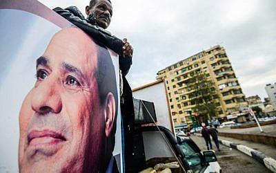 Un sympathisant du président égyptien Abdel Fattah el-Sissi se tient à l'arrière d'une camionnette arborant son portrait et ses haut-parleurs, sur la place Tahrir de la capitale, le 25 janvier 2018, alors que le pays marque le septième anniversaire du soulèvement de 2011 qui a mis fin au règne de 30 ans de l'ancien président Hosni Mubarak. (Crédit : AFP / MOHAMED EL-SHAHED)