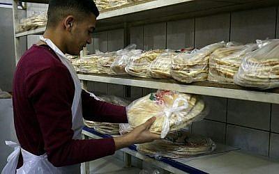 Un ouvrier jordanien emballe du pain dans une boulangerie de la capitale jordanienne Amman le 27 janvier 2018. (AFP / Khalil MAZRAAWI)