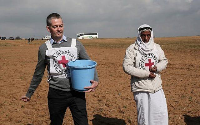 Guislain Defurne (à gauche), chef de la sous-délégation du Comité international de la Croix-Rouge (CICR) à Gaza, aide un agriculteur palestinien à semer des graines dans un champ, à l'est de Rafah, le 29 janvier 2018 (DIT KHATIB / AFP)