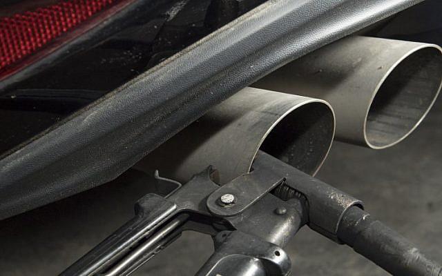 Un tuyau fixé au pot d'échappement d'une Golf Volkswagen diesel pour un test d'émission de gaz à  Ludwigsburg, dans le sud de l'Allemagne, le 7 août 2017 (Crédit : AFP PHOTO / THOMAS KIENZLE)