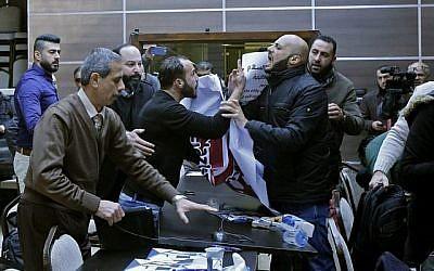 Des militants palestiniens perturbent une rencontre entre les membres d'une délégation économique américaine et le chef de la Chambre de commerce et d'industrie de Bethléem, dans la ville de Bethléem en Cisjordanie, le 30 janvier 2018. (AFP Photo/Musa Al-Shaer)