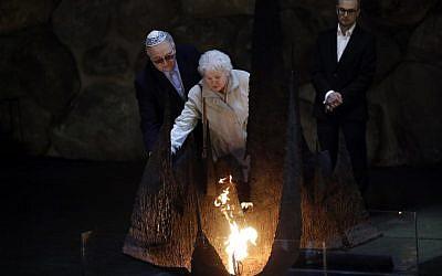 Alicja Mularska (C), la fille du défunt couple polonais Jan Dziadosz et Sabina Perzyna ranime la flamme éternelle après avoir reçu la citation de Juste parmi les Nations au nom de ses parents lors d'une cérémonie posthume les honorant ainsi que leur fils Aleksandr Dziadosz au mémorial de Yad Vashem, le Centre Mondial de la Mémoire de l'Holocauste, à Jérusalem, le 30 janvier 2018. (Crédit : AFP / THOMAS COEX)