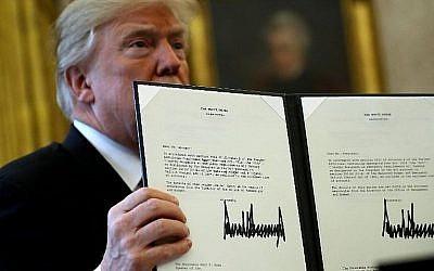 Le président américain Donald Trump brandit une copie de la législation avant de promulguer le projet de loi sur la réforme fiscale depuis le bureau ovale, le 22 décembre 2017 à Washington (Chip Somodevilla / Getty Images / AFP)