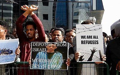 Les amis de Tesfe Kidane (aucun lien avec Helen Kidane), un demandeur d'asile érythréen déporté au Rwanda il y a deux ans, brandissent sa photo lors d'une manifestation devant l'ambassade rwandaise à Herzliya le 22 janvier 2018. Kidane a été assassiné en Libye en essayant de fuir vers l'Europe. (Melanie Lidman / Times of Israël)