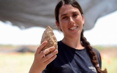 Maayan Shemer, directrice des fouilles pour l'Autorité israélienne des Antiquités, montre une hache taillée à la main d'un demi-million d'années à Jaljulia. (Crédit : Samuel Magal, autorisation AIA)