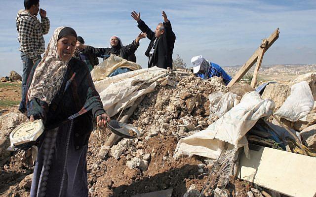 Les Palestiniens tentent de récupérer des objets dans les décombres d'une maison après avoir été détruit par des tracteurs de Tsahal près du village de Susya en Cisjordanie en 2011 (Crédit : Najeh Hashlamoun / Flash90)