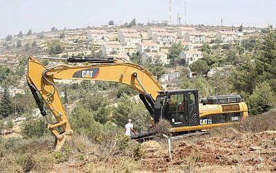 Un tracteur Caterpillar nettoyant des terres pour des constructions israéliennes en Cisjordanie, en 2012 (Oren Nahshon / Flash90)