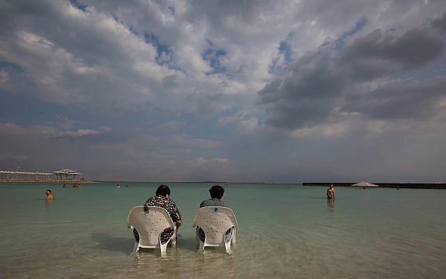 Des gens assis près de l'eau sur la plage de Hamei Zohar sur les rives de la mer Morte, le 10 novembre 2015 (Nati Shohat / Flash90)