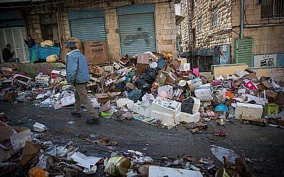 Les clients passent devant des piles d'ordures laissées par des ouvriers de la ville en grève, au Marché Mahane Yehuda de Jérusalem, le 7 janvier 2018. (Yonatan Sindel / Flash90)