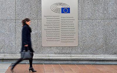 Une femme marche devant une plaque où le nom de parlement européen est décliné en plusieurs langues, celles des états-membres de l'institution, aux abords de l' Espace Leopold, le 25 février 2016 à Bruxelles, en Belgique (Crédit :  Ben Pruchnie/Getty Images via JTA)