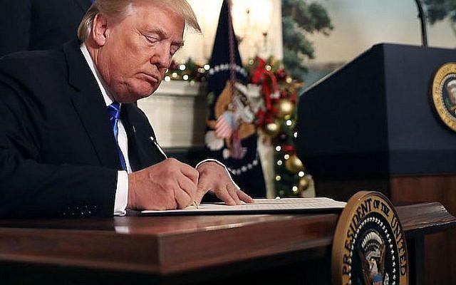Le président américain Donald Trump signe la déclaration de reconnaissance de Jérusalem comme capitale d'Israël, à la Maison Blanche, le 6 décembre 2017. (Crédit : Chip Somodevilla/Getty Images via JTA)