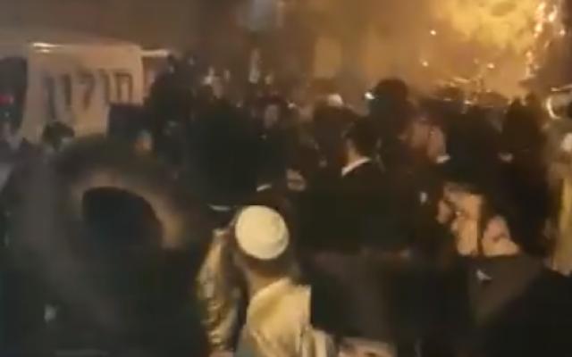 Des centaines de manifestants ultra-orthodoxes s'opposent à la police en tentant de bloquer un véhicule transportant un cadavre à une possible autopsie aux premières heures de la journée, le 21 janvier 2018 (Capture d'écran/Twitter)