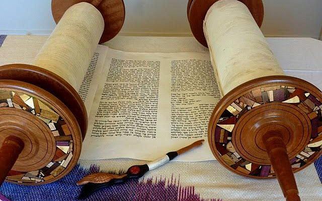 """Illustration : Une Torah ouverte, avec un """"doigt"""" sculpté à la main. (Courtesy Wendy Graff)"""