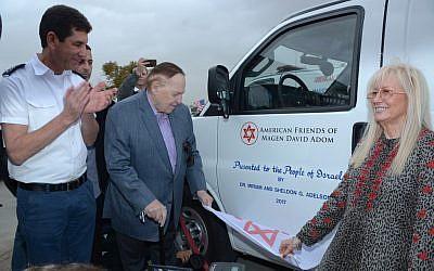(De gauche à droite) : le directeur du Magen David Adom, Avi Bin, Sheldon et Miriam Adelson regardent les modèles des cinq nouvelles ambulances blindées que les Adelsons ont données à quatre implantations en Cisjordanie. (Crédit : autorisation Magen David Adom)