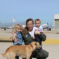 """Le major """"Tet"""" qui a été nommée première commandante d'un escadron de l'armée de l'air israélienne, poste avec ses enfants et un chien le 16 janvier 2018 (Crédit : Armée israélienne)"""