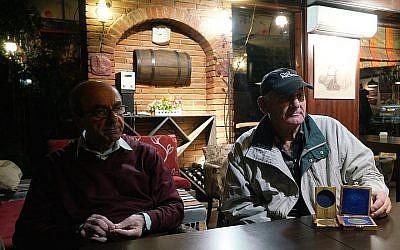 Rexhep Hoxha, à gauche, et Fatos Qoqja dans un bar à Tirania, en Albanie, le 8 novembre 2017. Qoqja est photographiée avec la médaille que son père a reçue pour avoir sauvé des Juifs pendant l'Holocauste. (Crédit : Cnaan Liphshiz / via JTA)