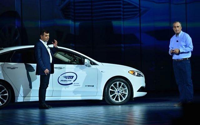 Le professeur Amnon Shashua, à gauche, vice-président d'Intel et directeur général de Mobileye, arrive sur scène au CES sur le siège arrière d'une voiture autonome durant le discours inaugural historique donné par le directeur-général d'Intel, Brian Krzanich, à droite. (Crédit :: Walden Kirsch/Intel Corp)