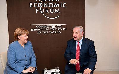 Le Premier ministre Benjamin Netanyahu rencontre la chancelière allemande Angela Merkel à Davos, en Suisse le 4 janvier 2018 (Crédit : Amos Ben Gershon/ GPO)