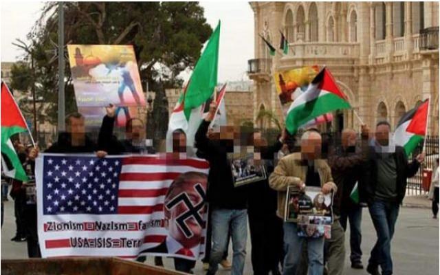 L'ex-officier de la police palestinienne (veste marron) brandi un panneau antisémite lors de la manifestation à Aida en Cisjordanie, près de Bethlehem, le 29 décembre 2017. (Police israélienne)