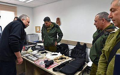 Le ministre de la Défense Avigdor Liberman, (à gauche), inspecte les armes à feu et le matériel militaire saisis lors d'une opération de l'armée à Hébron, en présence du responsable des relations avec les Palestiniens, le général Yoav Mordechai, (au centre), le chef d'état-major de l'armée israélienne, le général Gadi Eizenkot, (centre-droit) et le chef sortant du commandement central de l'armée israélienne, le général Roni Numa (à droite), lors d'une visite à Hébron le 27 février 2018. (Ariel Hermoni/Ministère de la Défense)